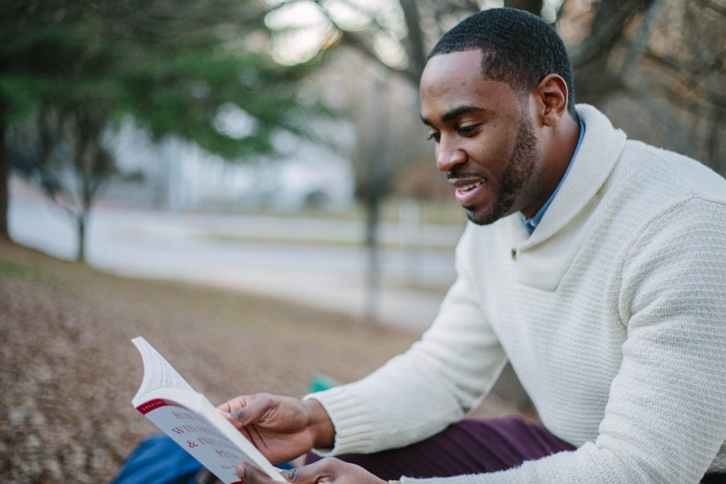 "Man Reading Dale Carnegie's ""How to Win Friends and Influence People"""